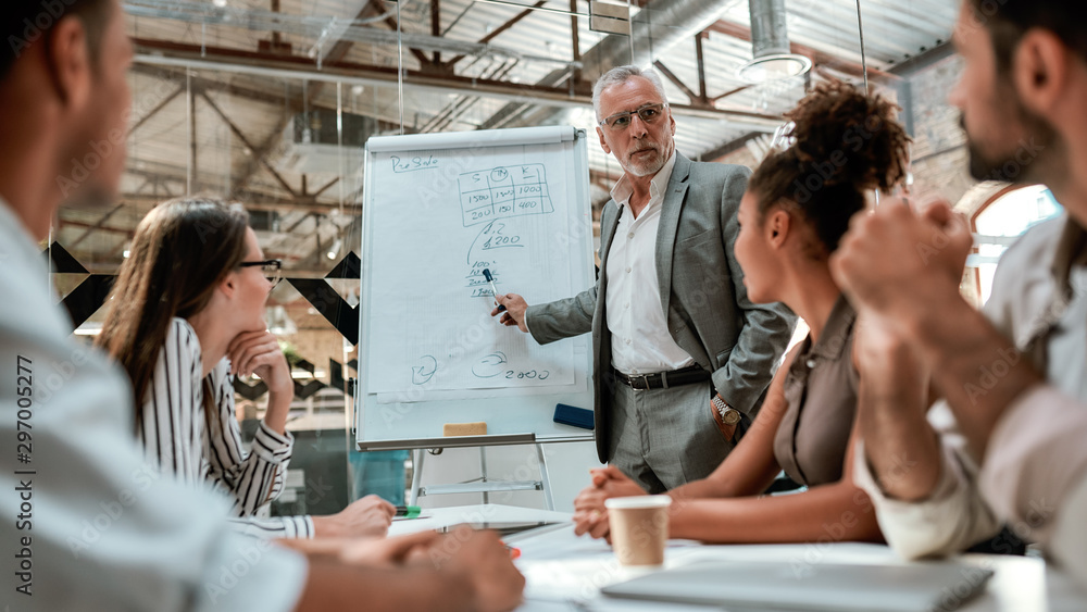 Fototapeta Business team. Confident mature businessman standing near whiteboard and explaining something to his young colleagues during meeting in the office