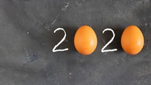 Figures 2020 Made With White Drown 2 And Two Whole Raw Orange Eggs Instead Of Zero Symbol On Chalk Board Black Background. Top View. Horizontal With Copy Space. Minimal Christmas Concept
