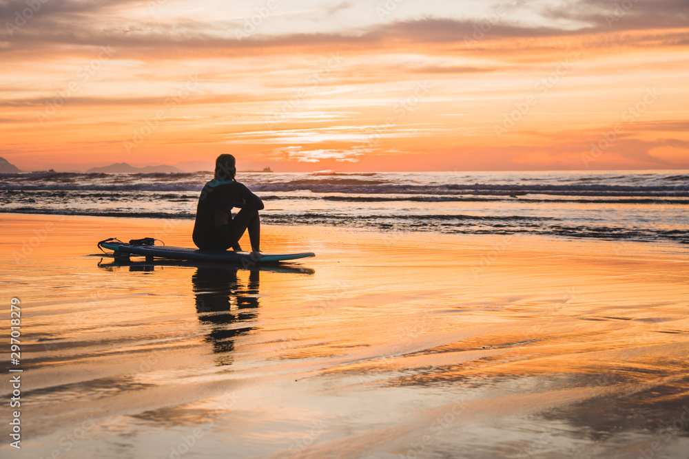 Fototapeta Silhouette of a surfer sitting on the beach of the Atlantic Ocean, near San Sebastian and Bilbao, North of Spain, Europe watching a dramatic stunning colorful sunset
