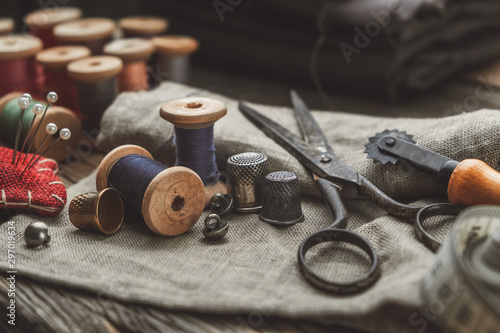 Photo Vintage sewing items: retro tailoring scissors, measuring tape, thimble, wooden spools of thread, cutting knife, cushion for including pins, needles and sewing accessories