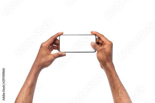 Fototapeta Black male hands taking photo on smartphone with blank screen obraz
