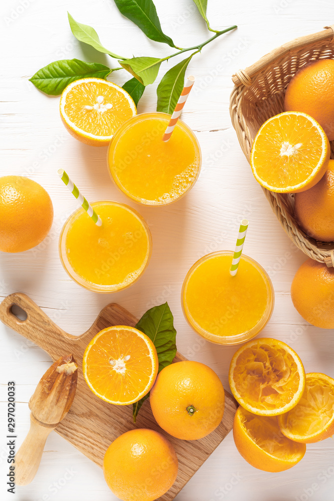 Fototapeta Orange juice. Freshly squeezed juice in glasses and fresh fruits with leaves, view from above