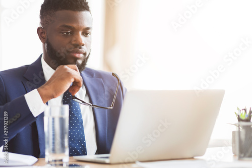 Close up of man in suit reading reports on laptop