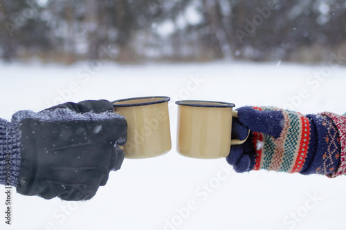 Poster de jardin The Two metal cups with hot tea in hands man's and woman's on a background of winter forest.