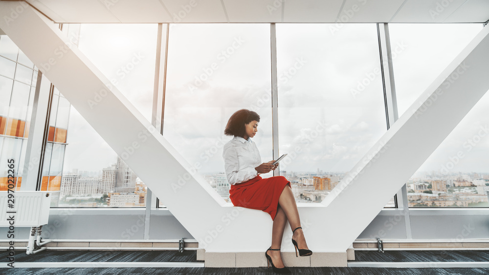 Fototapety, obrazy: A young African-American businesswoman with a digital tablet indoors of a bright passageway in an office skyscraper; a charming biracial female with a tablet pc near the window in a business high-rise