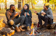 canvas print picture - Friends sitting beside fireplace in autumn forest, enjoying time together
