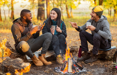 Fototapeta Friends sitting beside fireplace in autumn forest, enjoying time together