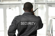 African-American Security Guard In Building, Back View