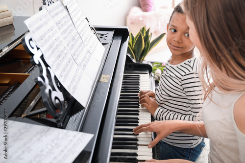 Woman teaching little African-American boy to play piano at home - 297026413