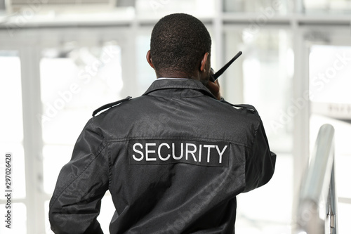Foto African-American security guard in building, back view