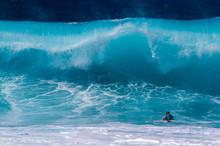 A Surfer Diving Under A Big Wave