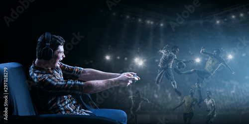 Fotografie, Tablou  Young man playing football video game