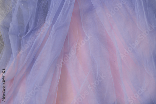 Fototapeta  Close up of thin blue tulle fabric on pink background