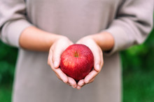 A Woman Holding A Fresh Red Apple In Hands