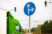 A Blue And White Round Sign In Germany Shows The Directions Straight Ahead And Right. Traffic Lights Show Green And A Truck Drives By.