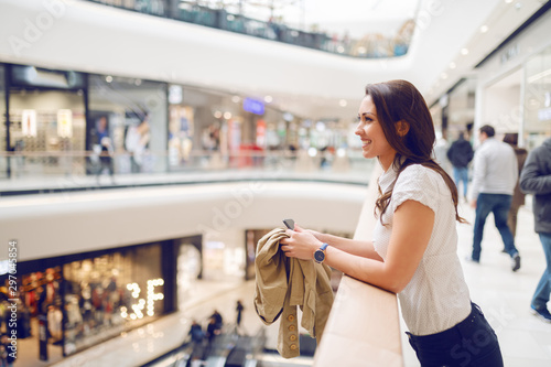 Fotomural  Side view of attractive brunette leaning on railing and holding jacket and smart phone while enjoying her time in shopping mall
