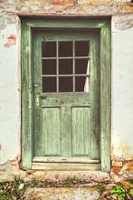 An Old Rotten Wooden Door On Crumbling House. Vintage Matte Look Effect.