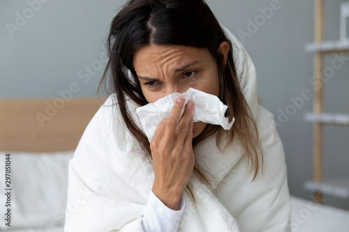 Unhealthy millennial mixed race girl wiping runny nose. Fototapet