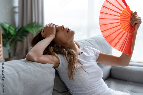 Fototapeta Exhausted girl using paper waver, suffering from hot summer weather. obraz