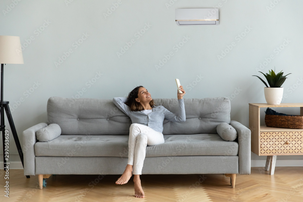Fototapety, obrazy: Joyful mixed race woman turning on cooler system air conditioner.
