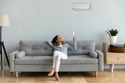 Joyful mixed race woman turning on cooler system air conditioner. Canvas Print