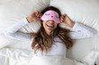 canvas print picture - Happy millennial woman lying in bed with sleeping mask.