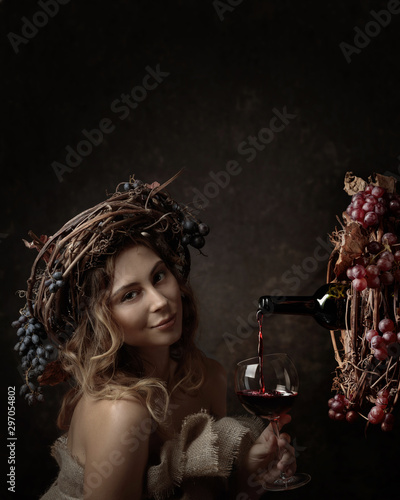 Attractive woman with glass of red wine in wine cellar . Vine wreath with blue grapes on a head. Red wine is poured from a bottle into a glass. Fototapete