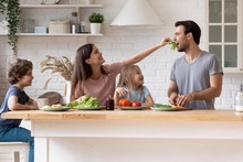 Happy Family Cooking Salad Together, Smiling Mother Feeding Father