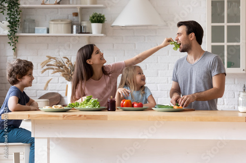 Obraz Happy family cooking salad together, smiling mother feeding father - fototapety do salonu