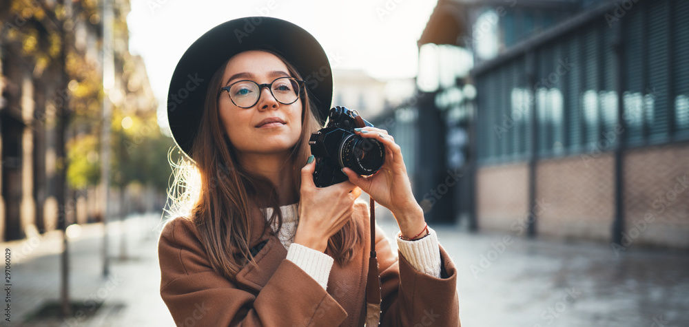 Fototapety, obrazy: Hobby photographer concept. Outdoor lifestyle portrait of pretty young woman in sun city in Europe with camera travel photo of photographer in glasses and hat take photo copy space mockup