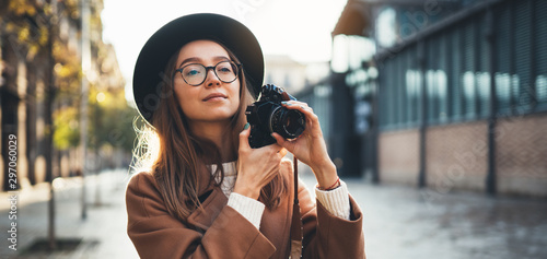 Fototapeta Hobby photographer concept. Outdoor lifestyle portrait of pretty young woman in sun city in Europe with camera travel photo of photographer in glasses and hat take photo copy space mockup obraz