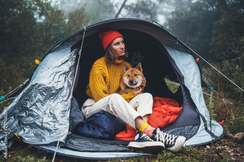 Fotografia tourist traveler in camp tent hugging shiba inu on background foggy rain forest,