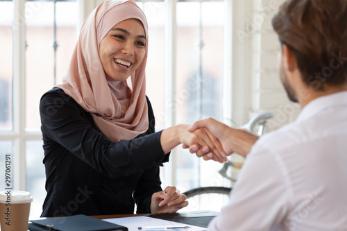 Vászonkép  Happy asian muslim hr handshake male applicant at interview meeting