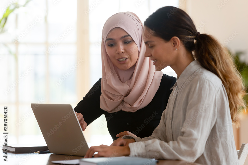Fototapety, obrazy: Asian muslim female mentor teaching caucasian intern explaining computer work