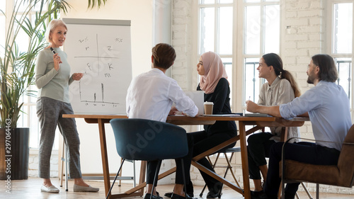 Photographie  Middle aged female mentor teaching multicultural employees with flip chart