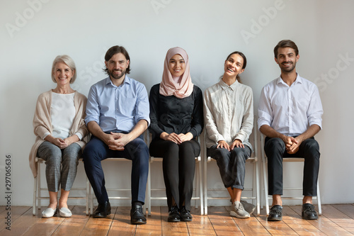 Fototapety, obrazy: Smiling multicultural professional business people sit on chairs in row