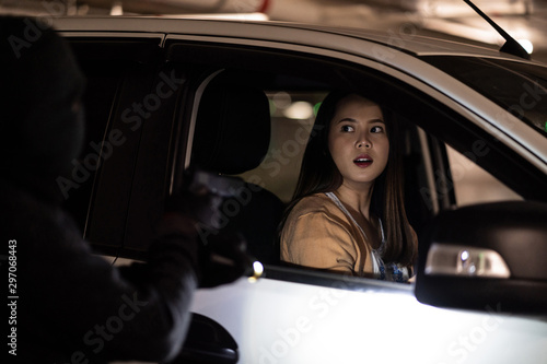 Fotografía  Asian woman she is scared She is being threatened to rob a car.