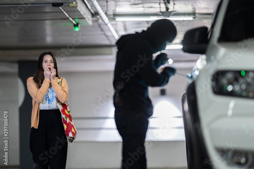 Fotomural  Woman is shocked. She is being robbed of her car.at night parking