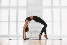 Young Beautiful Woman Practicing Yoga Near Floor Window In Yoga Studio, Standing In Bridge Exercise, Urdhva Dhanurasana Pose. Harmony, Balance, Relaxation, Healthy Lifestyle Concept