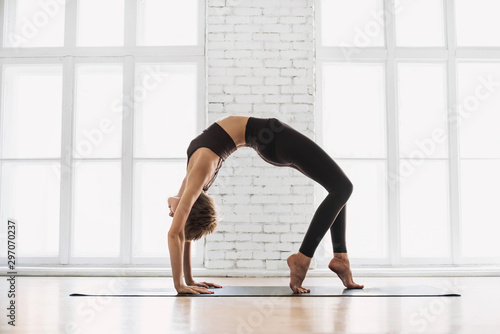 Obraz Young beautiful woman practicing yoga near floor window in yoga studio, standing in Bridge exercise, Urdhva Dhanurasana pose. Harmony, balance, relaxation, healthy lifestyle concept - fototapety do salonu