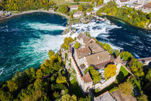 Red Roofs And Towers Of Cliff-top Schloss Laufen Castle, Laufen-Uhwiesen. Rhine Falls Or Rheinfall, Switzerland. Bridge And Border Between The Cantons Schaffhausen And Zürich. Panoramic Aerial View