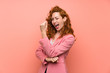 Redhead woman in suit over isolated pink wall making strong gesture