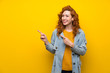 Redhead woman over isolated yellow background pointing finger to the side