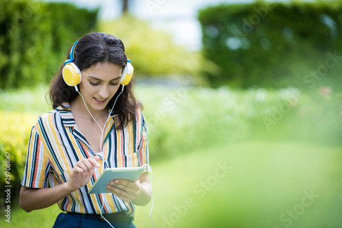 Foto  Portrait of a beautiful woman has listening to music with smiling and relax in the garden