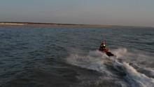 Rescue Brigade Jetski With A Lifeguard Hanging On Moving Fast Through Sea
