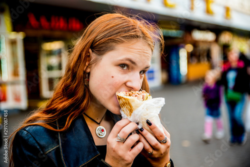 In de dag Kruidenierswinkel portrait of young teenager redhead girl with long hair eating chicken shawarma on street