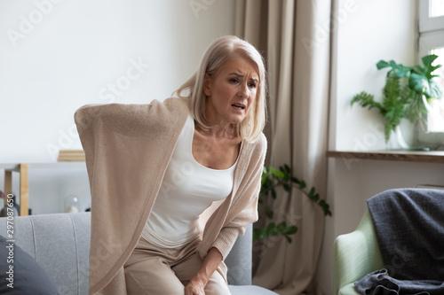 Cuadros en Lienzo Worried upset mature woman feel hurt sudden back ache