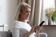 canvas print picture Happy middle aged woman using mobile apps texting at home