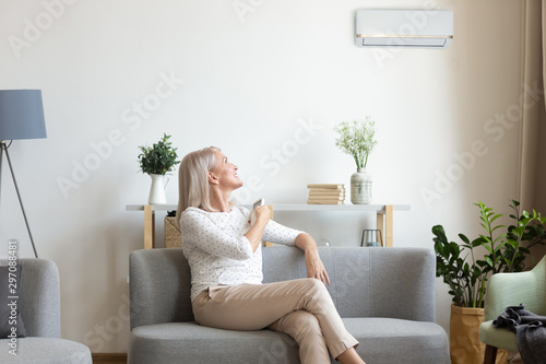 Fotomural  Middle aged woman switching on air conditioner in living room