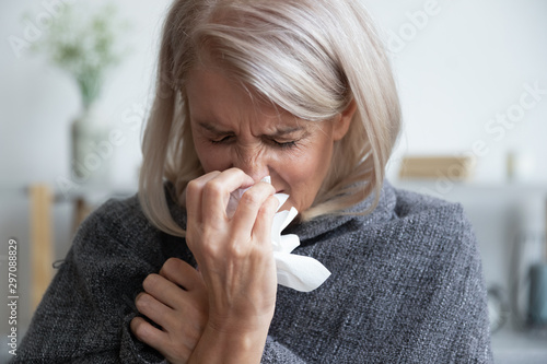 Foto auf AluDibond Logo Ill mature woman covered with blanket blowing running nose sneeze
